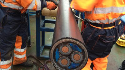 OMPA offshore personnel handling subsea power cable